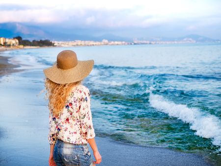 blondy: A young blondy girl in a sun-hat and flower-printed blowse staying at the sea coast and looking forward to the horizon