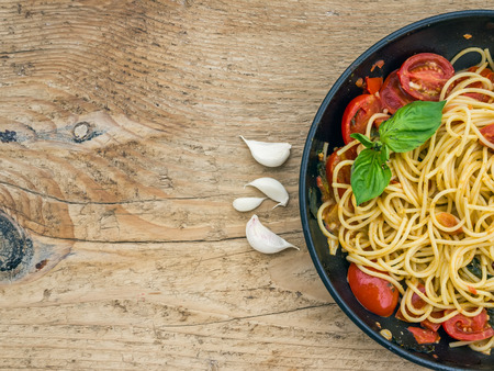 eating pasta: Pasta with tomatoes and basil on a wooden desk Stock Photo