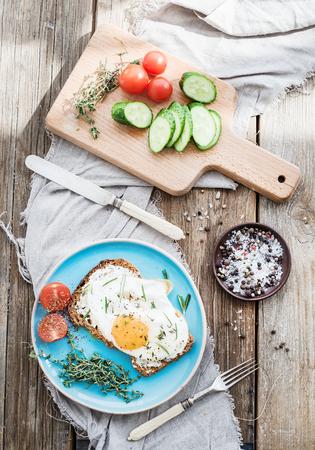 petit dejeuner: Petit d�jeuner ensemble. Andwich � grains entiers avec des ?ufs frits, des l�gumes et des herbes sur la table en bois rustique, l'humeur du matin, vue de dessus Banque d'images