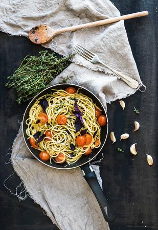 comida italiana: Espaguetis de pasta con salsa de pesto, albahaca, cereza-tomates, el ajo y el tomillo en una olla de cocción en la vieja mesa oscuro del grunge, vista desde arriba Foto de archivo