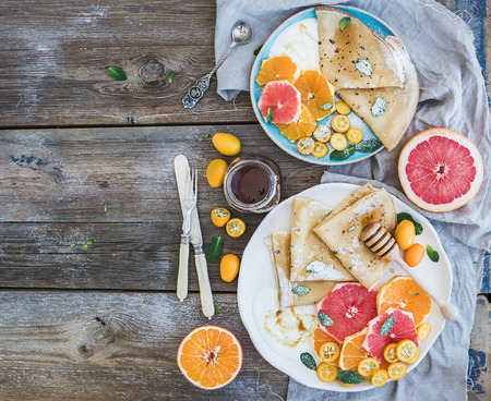 Spring vitamin breakfast set. Thin crepes or pancakes with fresh grapefruit, orange, kumquat, honey, cream and mint leaves over a rustic wood background, top view Banco de Imagens