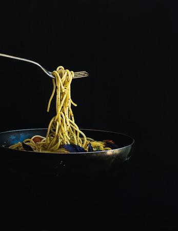 italienisches essen: Hot Spaghetti mit Tomaten in der Küche Pfanne und Gabel auf schwarzem Hintergrund