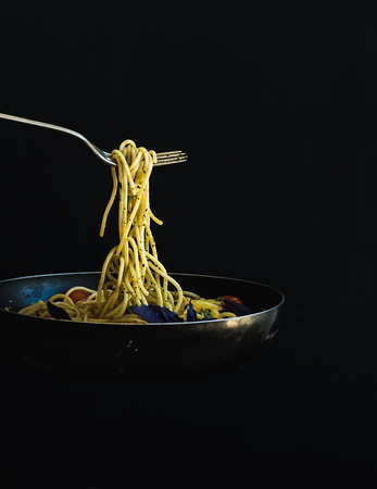 black dish: Hot spaghetti with tomatoes in cooking pan and fork on black background Stock Photo