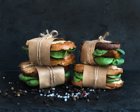 gourmet burger: Cured chicken and spinach whole grain sandwiches placed one on another wrapped in craft paper and tied with a decoration rope  with spices and black stone background Stock Photo