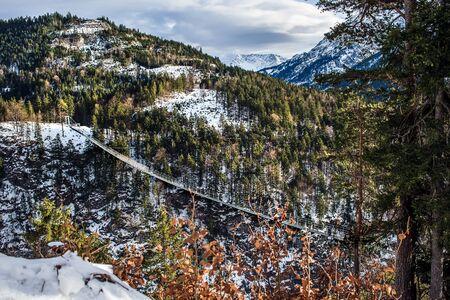 baratro: Un ponte su un abisso che collega il castello Ehrenberg alla montagna di fronte nelle Alpi tirolesi, in Austria, in inverno Archivio Fotografico