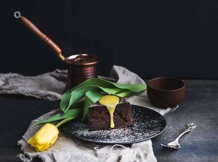 Perfect morning set for woman. Piece of truffle chocolate cake with lemon curd icing, pot of hot coffee and yellow tulip on dark backdrop. Dutch still life photo