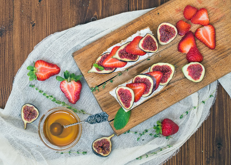 bawl: Fresh strawberries, figs, mint leaves, thyme and a small bawl of honey ob a wooden cutting board over a piece of linen fabric and medium-dark wooden background