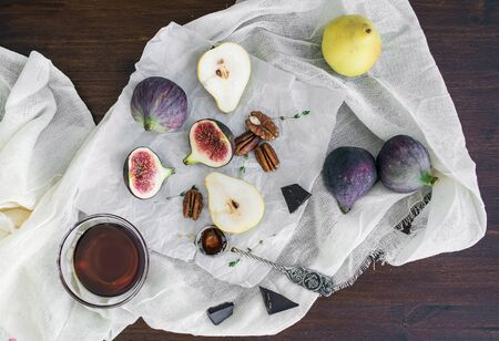 Fresh figs, bitter chocolate, pears and pekan nuts with honey on a wooden board and white tissue photo