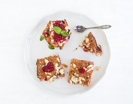 meant: Cottage cheese raspberry pie bars with fresh raspberry jam and meant leaves on a white plate Stock Photo