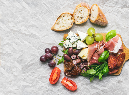 spanish village: Wine set consisting of smoked meat, sausages, cheese, grapes, cherry-tomatoes, olives, green basil leaves, arugula, dried tomatoes and baguette slices on arustic wood board over a wtite paper background Stock Photo