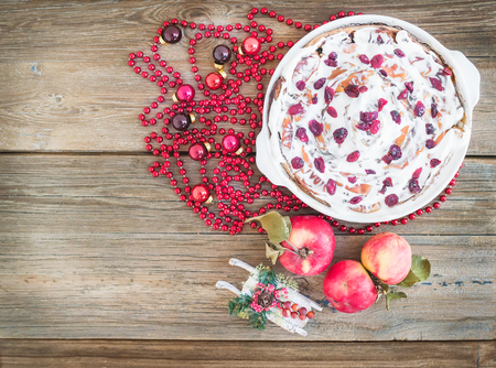 rustic  wood: Apple, cranberry and cinnamon roll cake with creamy icing and Christmas decoration over a rustic wood background with a copy space Stock Photo