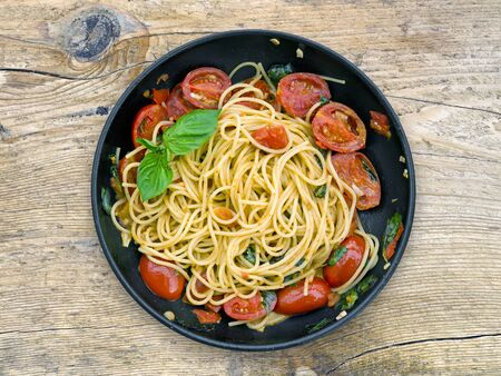 A pan of spaguetti with tomatoes and basil on the old wooden surface Banco de Imagens