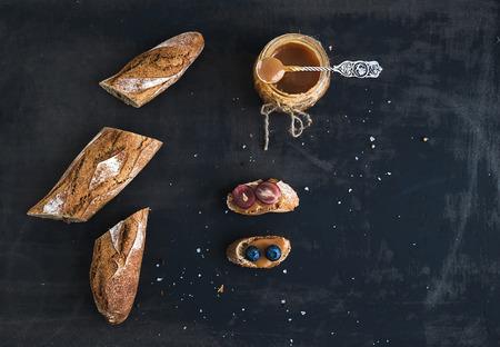 sal: Franc�s corte baguette en pedazos, s�ndwiches con uvas rojas, ar�ndanos y salsa de caramelo salada en r�stica fondo oscuro. Vista superior, espacio de la copia