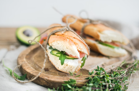 tied up: Salmon and avocado sandwiches with fresh thyme in baguette tied up with a decoration rope on a rustic wooden board over rough wood background. Top view