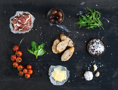 select: Ingredients for sandwich with smoked meat, baguette, basil, arugula, olives, cherry-tomatoes, parmesan cheese, garlic and spices over black grunge background. Top view