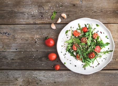 Ensalada de rúcula, tomates cherry, semillas de girasol y las hierbas en la placa de cerámica blanca sobre fondo de madera rústica, vista desde arriba, copia espacio