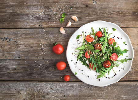 Salad with arugula, cherry tomatoes, sunflower seeds and herbs on white ceramic plate over rustic wood background, top view, copy space