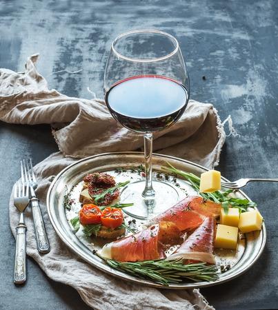 pan y vino: Establece aperitivo Vino. Copa de vino tinto, vajilla vintage, brushetta con la cereza, tomates secos, rúcula, parmesano, carne ahumada en bandeja de plata sobre la superficie del grunge rústico. Acercamiento