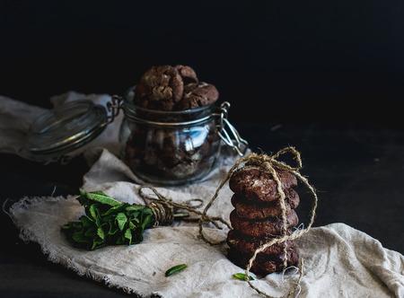 chocolate cookie: Oscuras galletas de chocolate con menta fresca sobre fondo oscuro