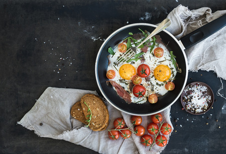 Pan of fried eggs, bacon and cherry-tomatoes with bread on dark table surface, top view