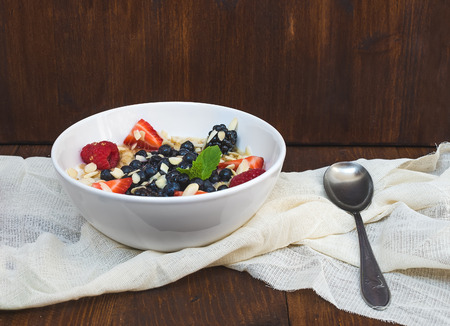 bawl: A bawl of oat porridge with fresh berries, honey, almond petals and leaves of mint over a piece beige linen fabric on a dark wooden background