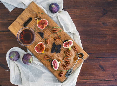 pekan: Fresh figs, bitter chocolate and pekan nuts with honey on a wooden board and white tissue