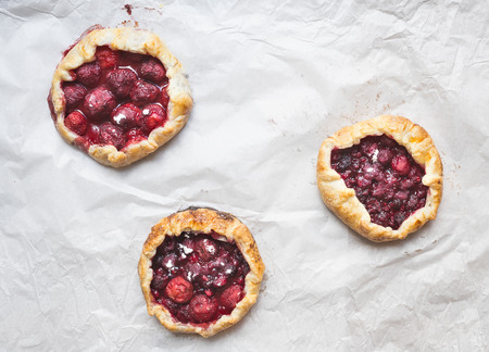 galettes: Small berry galettes on white paper background Stock Photo
