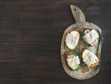 chiken: Healthy breakfast set consisting of chiken and green salad sandwiches on a rustic wooden board over dark rough wood background with a copy space. Top view Stock Photo