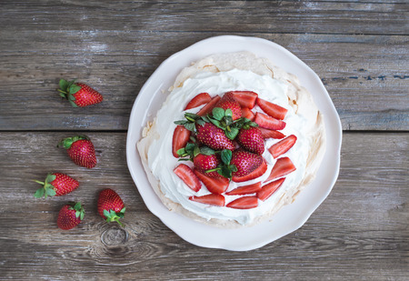 Rustic Pavlova cake with fresh strawberries and whipped cream over a rough wood background. Top view photo