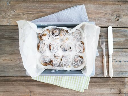 rustic  wood: Cinnamon buns with cream-cheese icing in a baking dish over a rustic wood background
