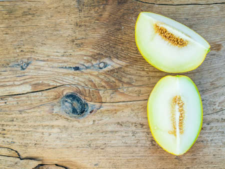 two pieces: Two pieces of ripe fresh melon on a wooden background