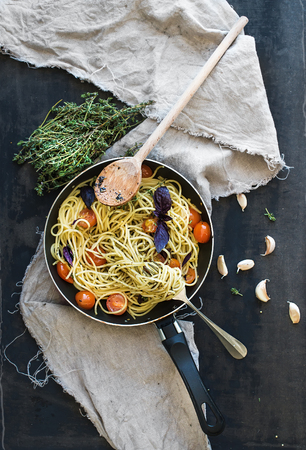 linguine pasta: Pasta spaghetti with pesto sauce, basil, cherry-tomatoes, garlic and thyme in a cooking pan on old grunge dark table, top view Stock Photo