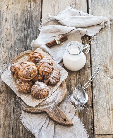 Cinnamon buns with sugar powder on a rustic wooden board, jug of milk, on dark grunge backdrop photo