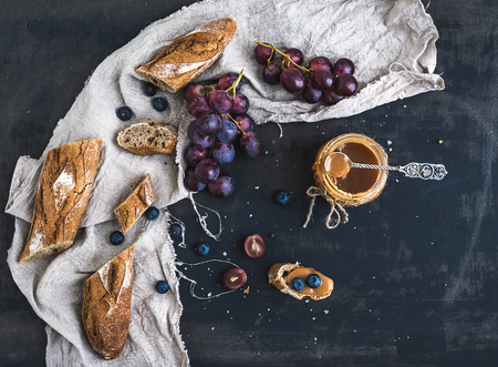 breakfast food: French baguette cut into pieces, red grapes, blueberry and salty caramel sauce on linen towel over rustic dark background with a copy space. Top view