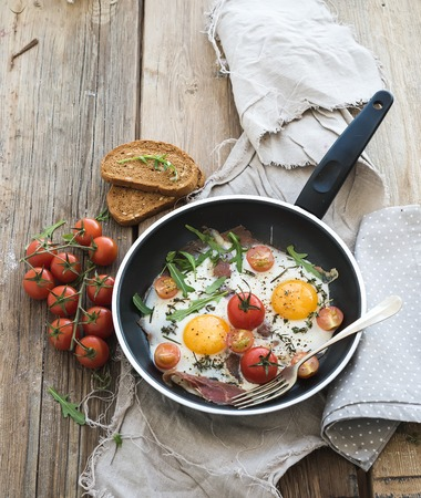 Pan of fried eggs, bacon and cherry-tomatoes with bread on rustic wood table surface, top view Banco de Imagens