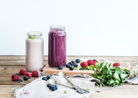Fresh healthy smoothie with blueberries, raspberries in glass jars and mint over rustic wood background