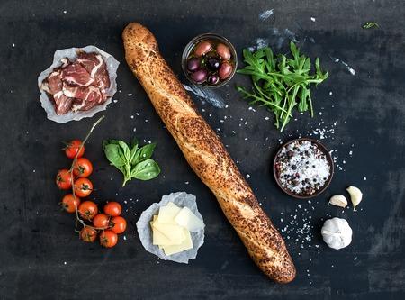 bocadillo: Ingredientes para sándwich con carne ahumada, baguette, albahaca, rúcula, aceitunas, tomates cherry-, queso parmesano, ajo y especias sobre fondo negro del grunge. Vista superior