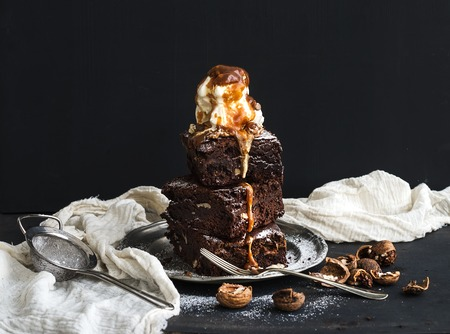 backdrop: Fudgy Brownies tower with salted caramel, walnuts and ice-cream on vintage metal plate. Dark backdrop