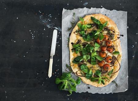 dough: Pizza hecha en casa rústica con corderos fresca lechuga, champiñones y tomates cherry-sobre el fondo oscuro del grunge, vista desde arriba, copia espacio Foto de archivo