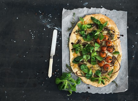 Rustic homemade pizza with fresh lambs lettuce, mushrooms and cherry-tomatoes over dark grunge background, top view, copy space