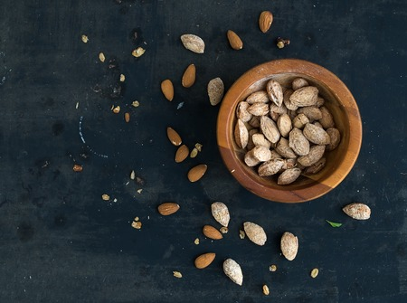 nutshell: Wooden bowl of salty almond nuts in nutshell grunge dark backdrop, top view, copy space