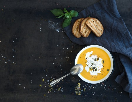Pumpkin soup with cream, seeds, bread and fresh basil in rustic metal plate on grunge black background. Top view, copy space