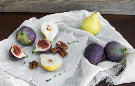 pekan: Figs, pears and pekan nuts on a white tissue on a wooden table surface