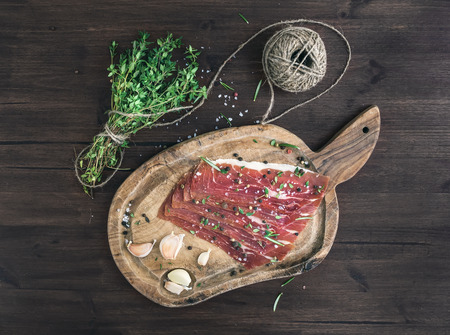 Cured pork meat (prosciutto) on a rustic woodem board with garlic, spices and thyme over a dark wood background. Top view photo