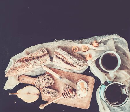 cezve: Breakfast set: a pot (cezve) of coffee, a cup on a kitchen towel, kumquats, pears, baguette slices with butter cream and honey on a rustic wooden board over a black backdrop with a copy space. Top view