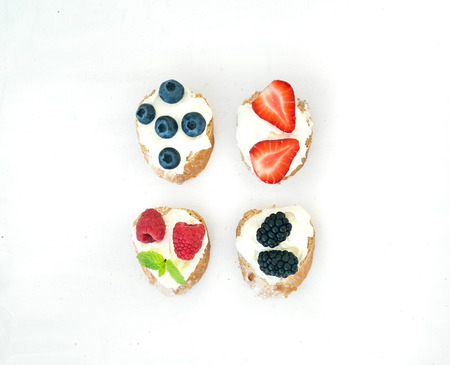 sanwich: Set of small sweet sandwiches with cream-cheese and fresh forest berries over a white background with a copy space. Top view