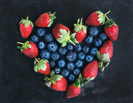 Saint Valentines day greeting berry set: fresh garden straberries and blueberries places together in a shape of heart over a rough black stone background. Top view Stock Photo
