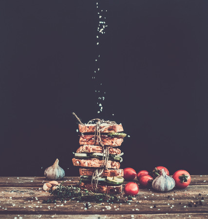 strewed: Sandwiches with smoked meat, cucumber and herbs tied with a rope, placed one over another. Salt is being strewed on them from above on them