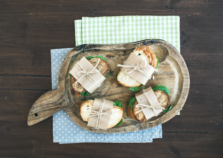 chiken: Healthy breakfast set consisting of chiken and green salad sandwiches on a rustic wooden board over dark rough wood background. Top view Stock Photo
