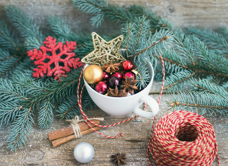 colrful: Christmas (New Year) decoration set: a cup full of colrful Christmas tree toys, cinnamon sticks and a decoration rope on a rustic wood background. Selective focus